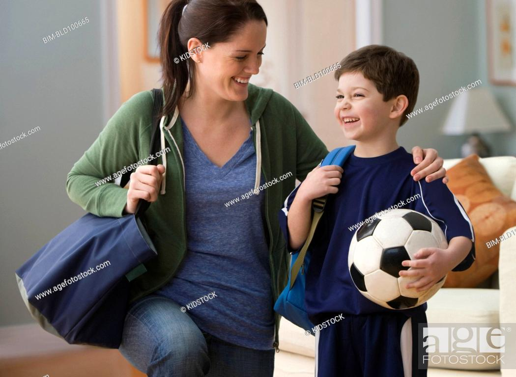 Stock Photo: Caucasian mother talking to son holding soccer ball.
