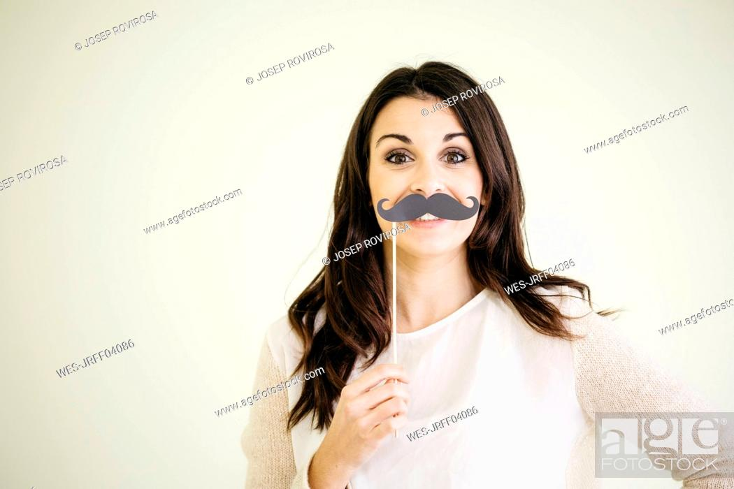 Stock Photo: Portrait of young woman with fake moustache.