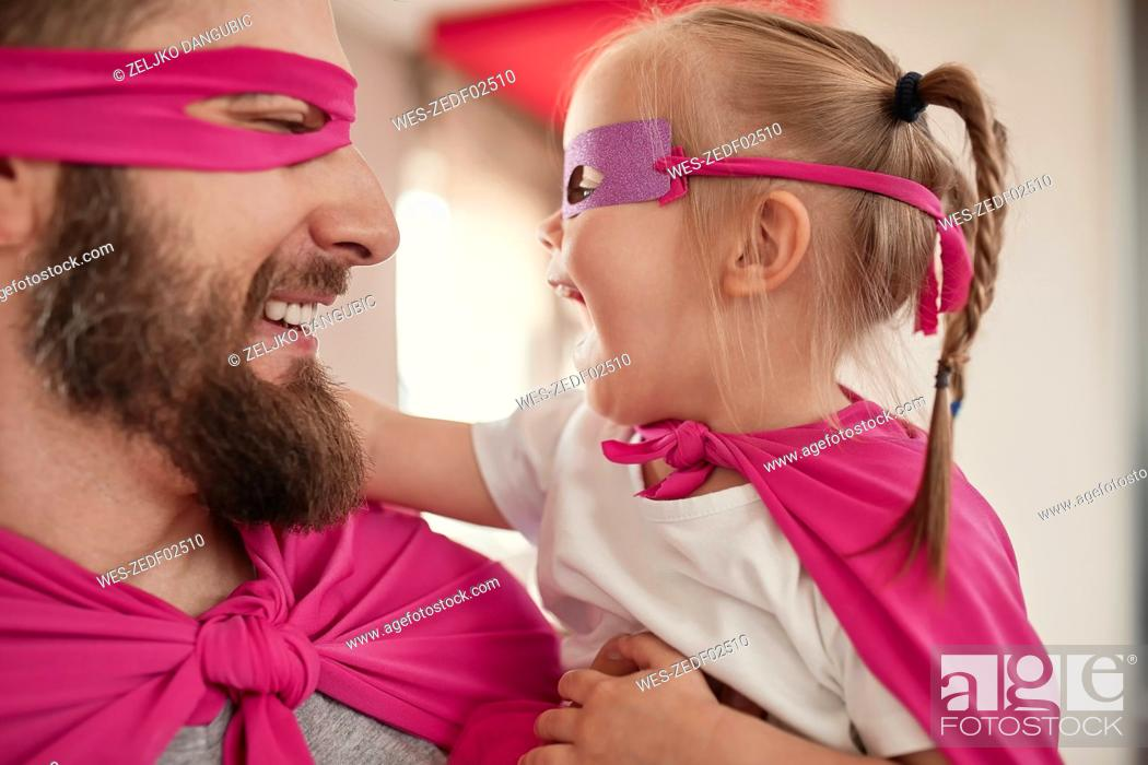 Stock Photo: Father and daughter playing super hero and superwoman.