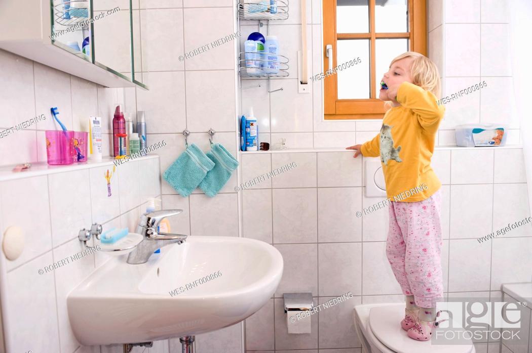 Stock Photo: Girl standing on toilet, brushing teeth in bathroom.