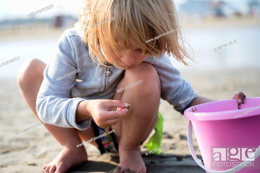Stock Photo: Little girl with bucket on the beach.