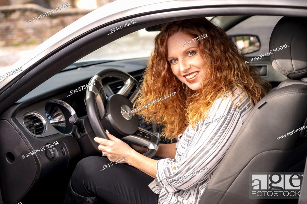 Stock Photo: A beautiful 41 year old redheaded woman in the driver's seat of a car.