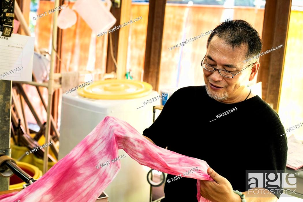Stock Photo: Japanese man wearing glasses standing in a textile plant dye workshop, holding piece of pink fabric.