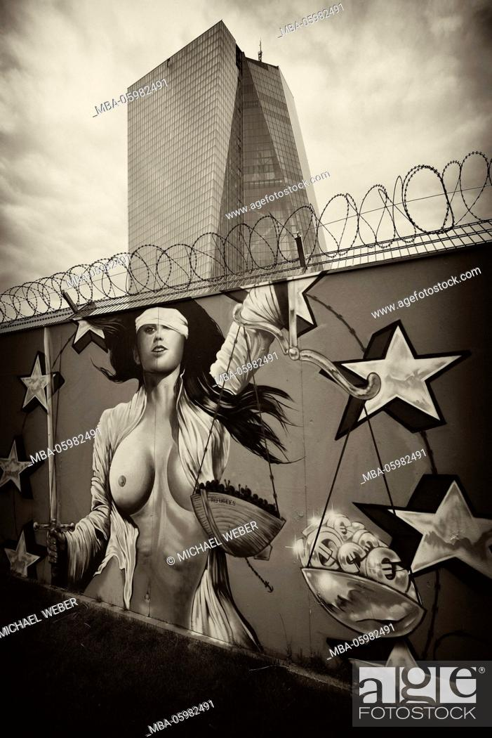 Stock Photo: Euro-sceptic graffiti on site fence with barbed wire, half-blind (Lady) (Lady) Justice, new building of the European Central Bank, ECB, Ostend.