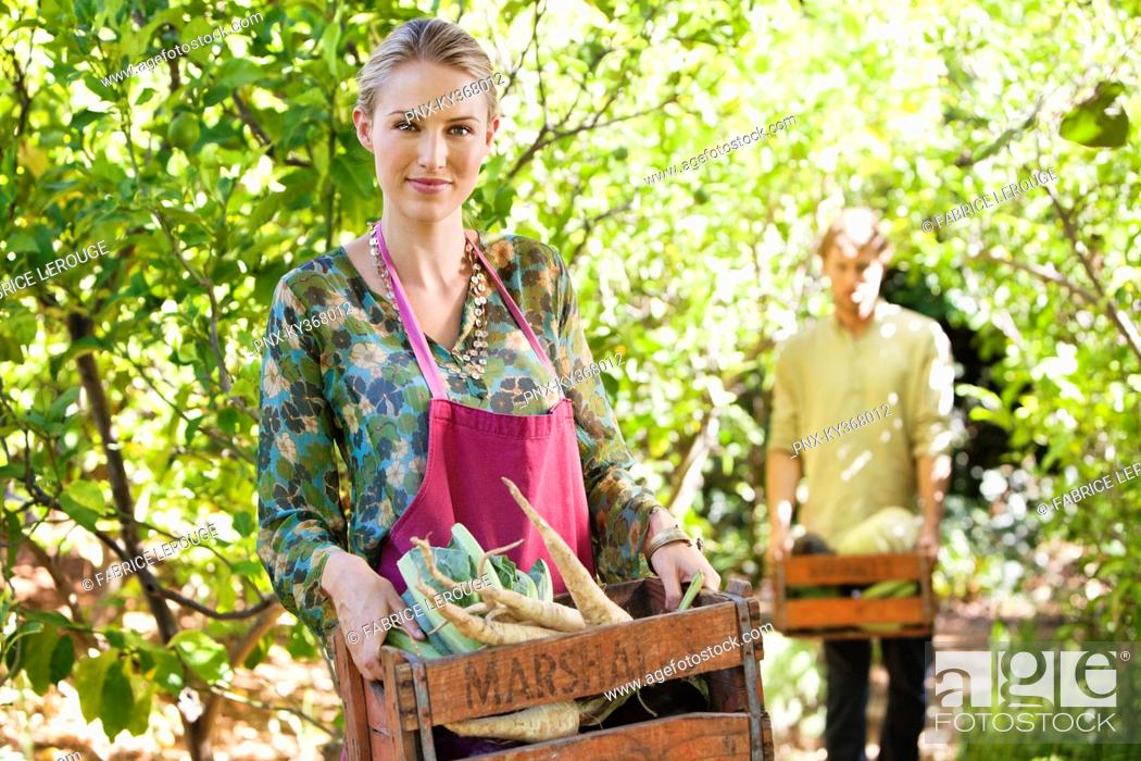 Stock Photo: Smiling woman holding a crate of radish.