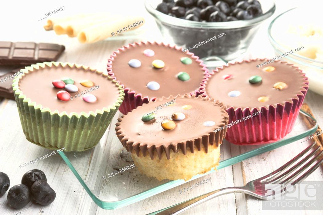 Photo de stock: chocolate covered muffins modern wooden stage with chocolate and cinnamon and blueberries.