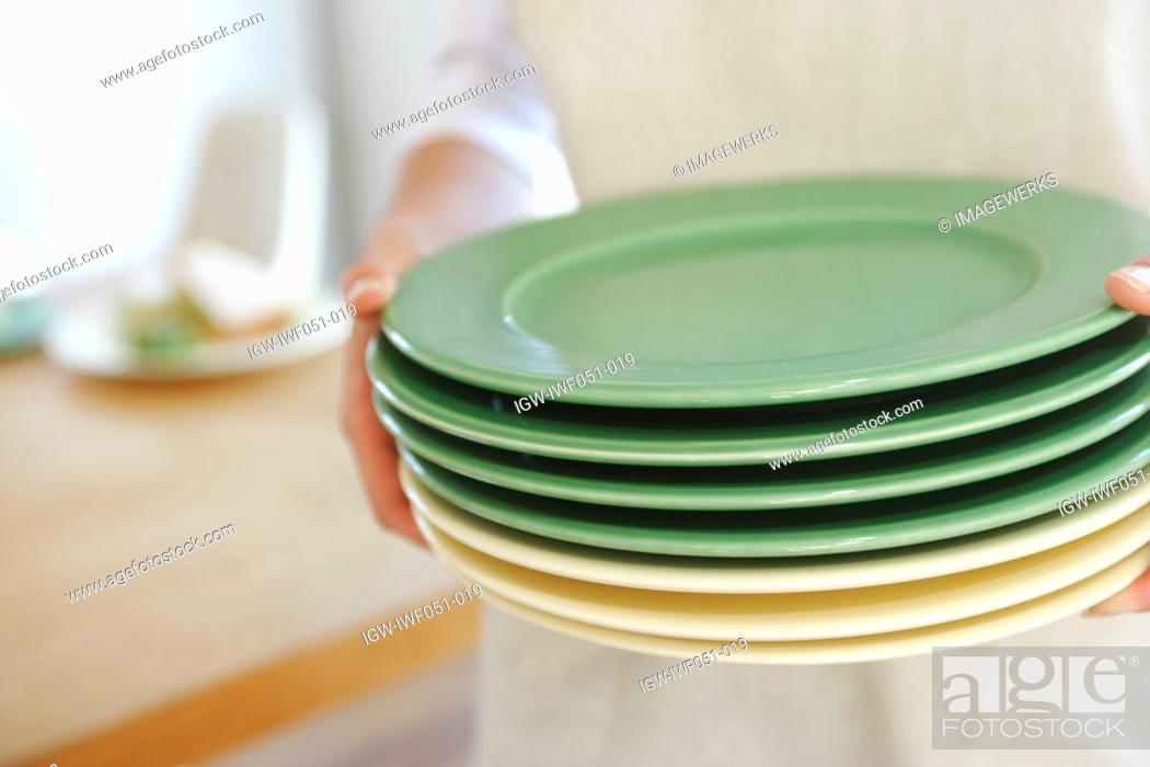 Stock Photo: Teenage girl 14-15 holding stack of plates.
