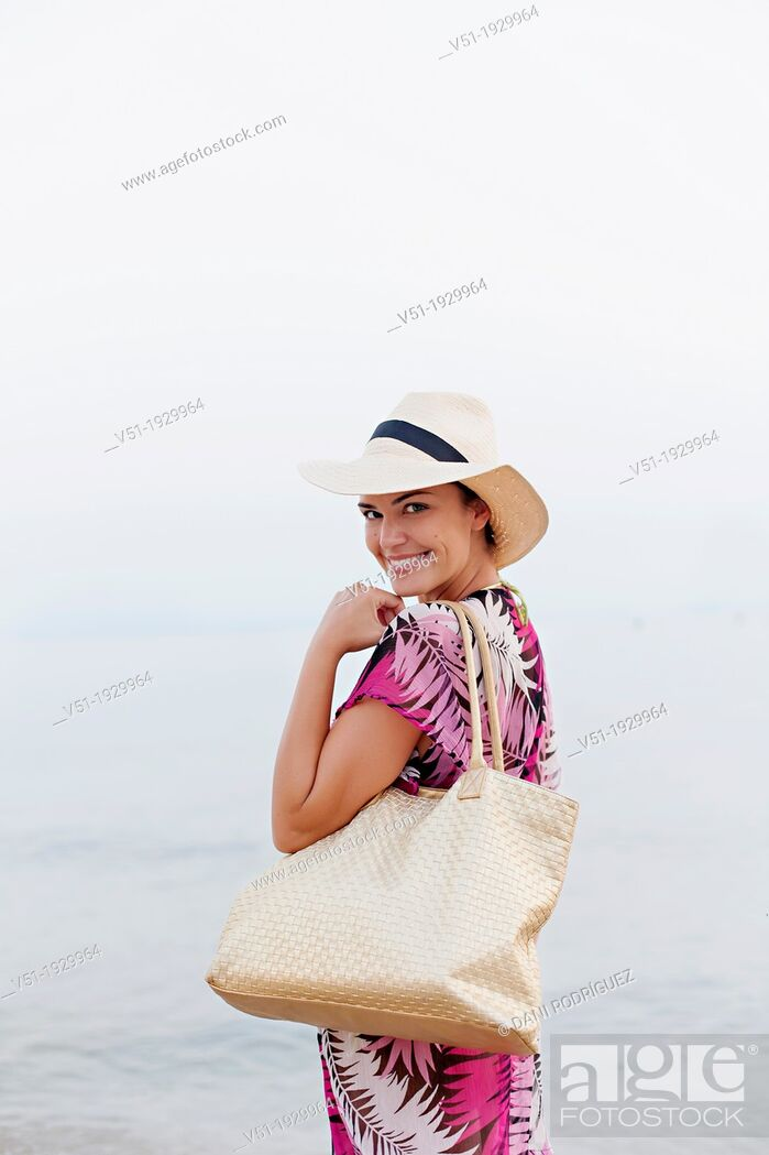 Stock Photo: Woman with hat arriving at the beach smiling at camera.