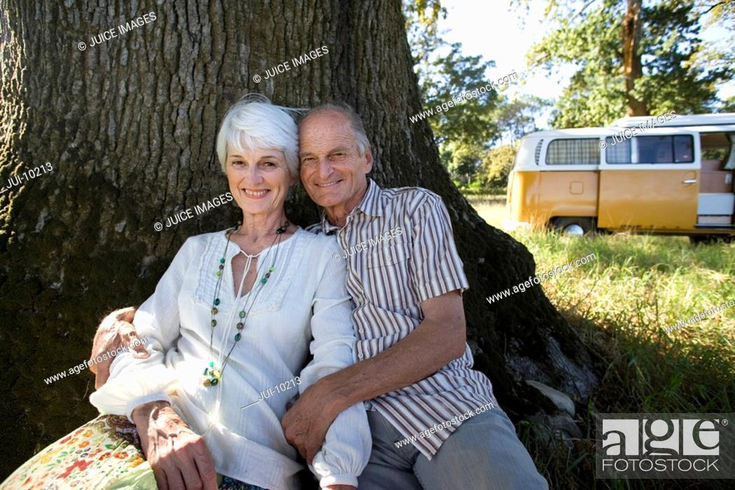Stock Photo: Senior couple reclining against tree in field, camper van in background, smiling, portrait.