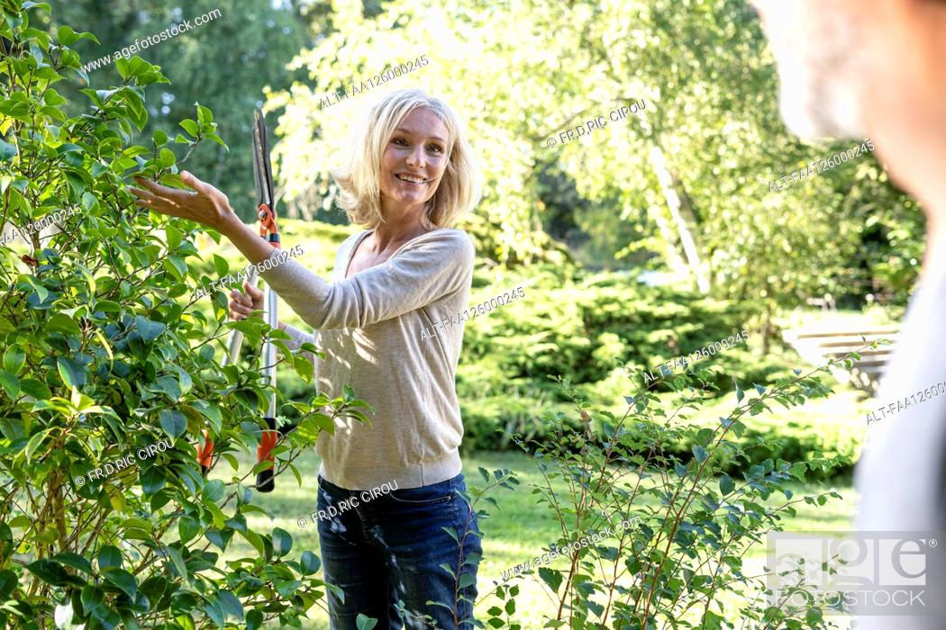 Photo de stock: Smiling mature woman with secateurs looking at her husband in backyard.