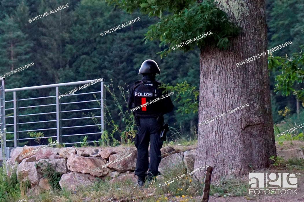 Imagen: 13 July 2020, Baden-Wuerttemberg, Oppenau: A policeman stands in front of a wooded area on a road near Oppenau. The day before.