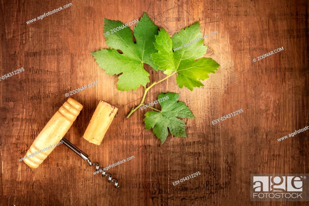 Stock Photo: Wine design template. A vine leaf with a vintage corkscrew and a cork, shot from the top on a dark rustic wooden background with a place for text.