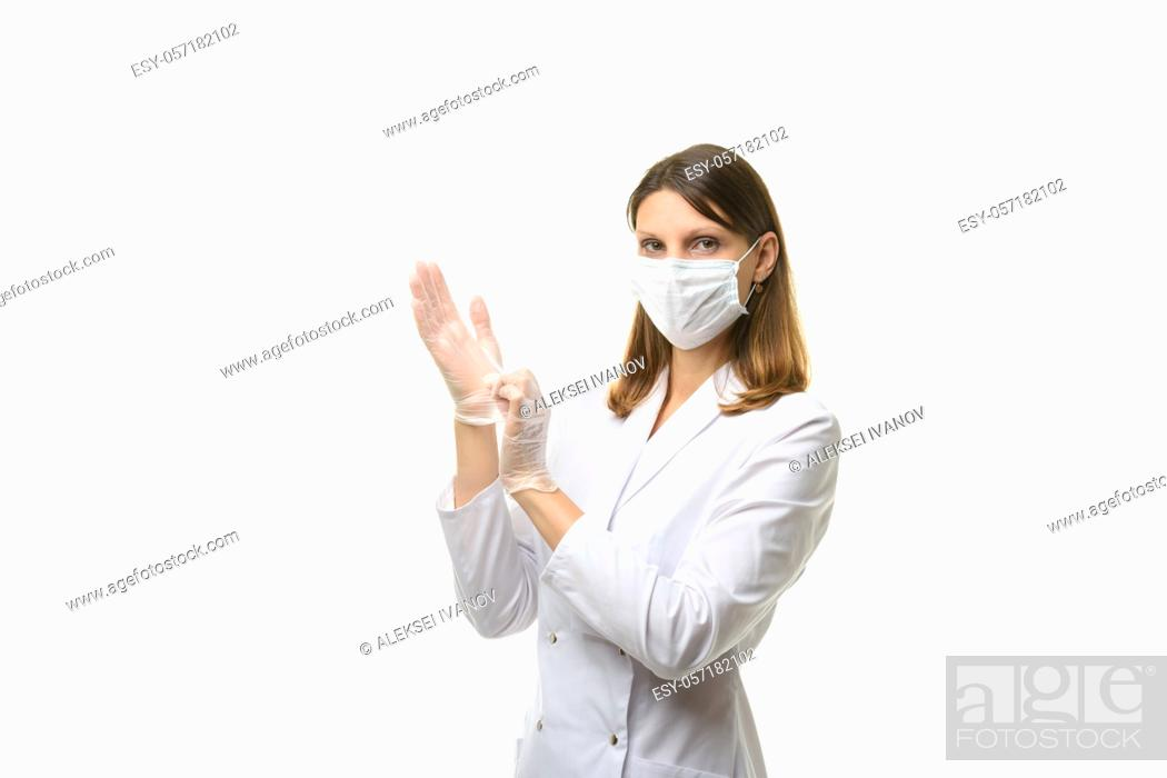 Stock Photo: Girl doctor puts on transparent medical gloves on her hands, and looks into the frame.