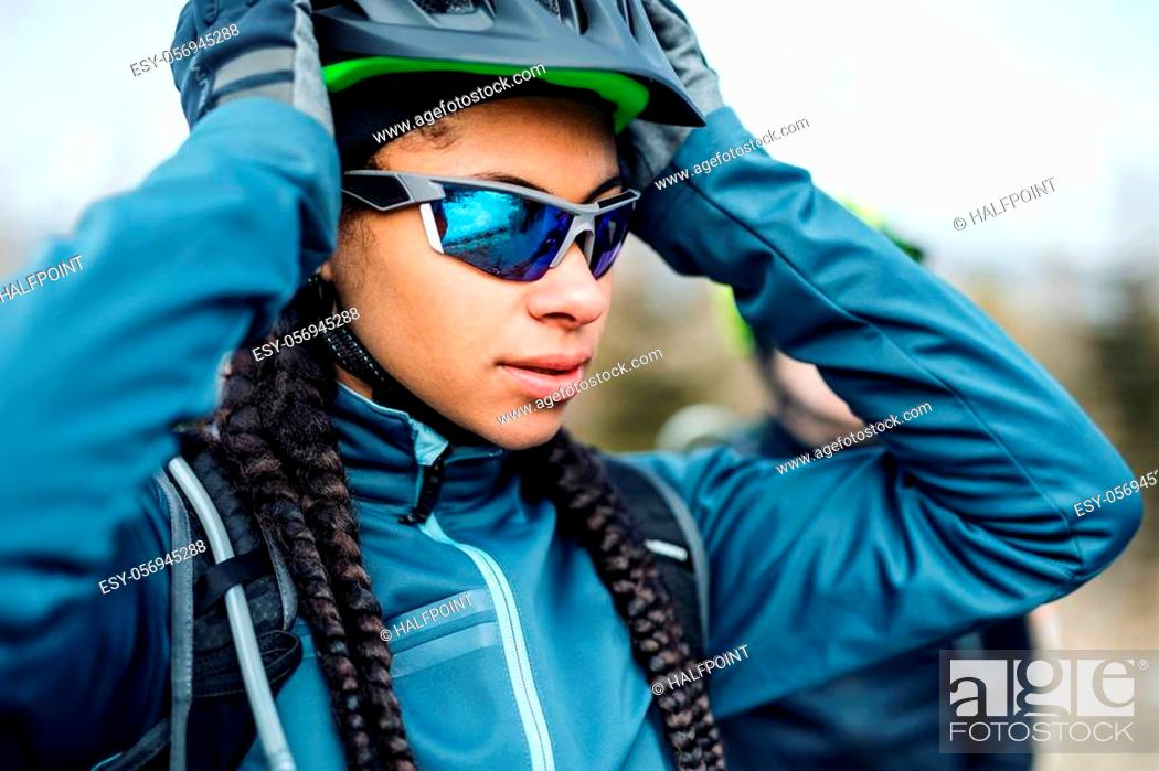 Stock Photo: Female mountain biker standing on road outdoors in winter, putting on sunglasses.