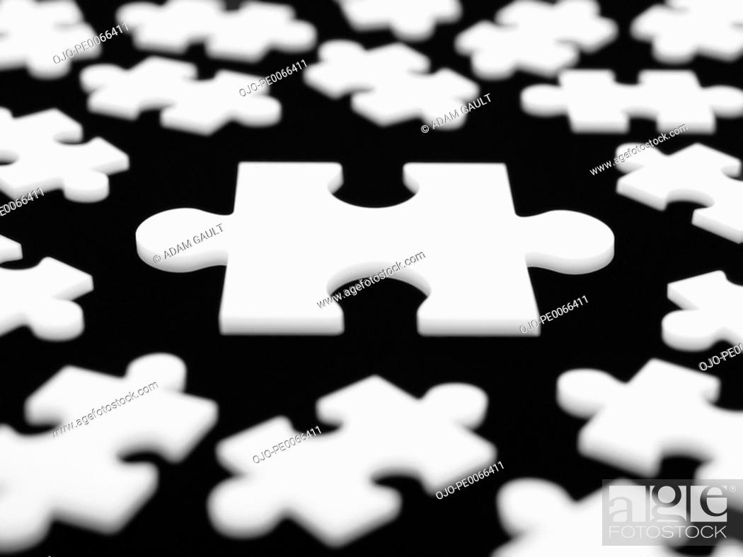 Stock Photo: Large puzzle piece surrounded by smaller ones.