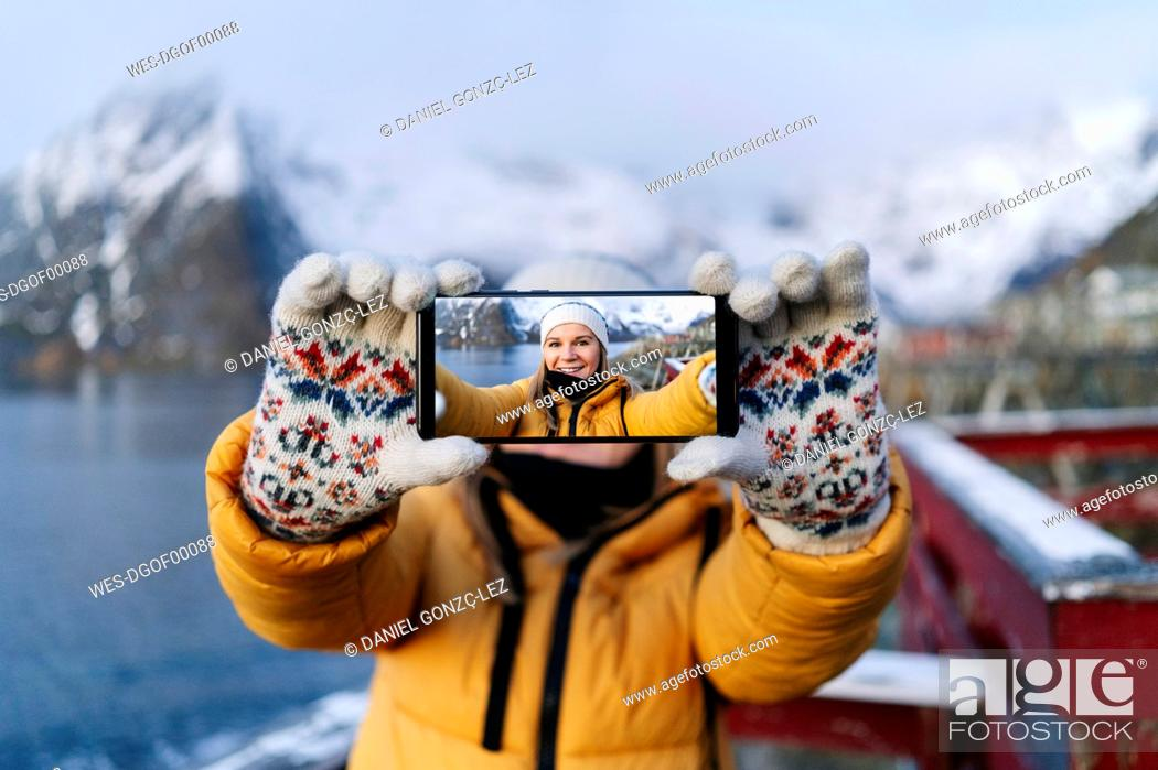 Photo de stock: Portrait of smiling tourist taking a selfie at Hamnoy, Lofoten, Norway.