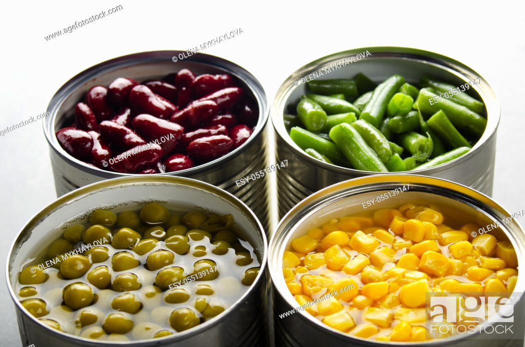 Stock Photo: Canned kidney beans, green beans, peas and corn in opened tin cans on kitchen table. Non-perishable foods background.