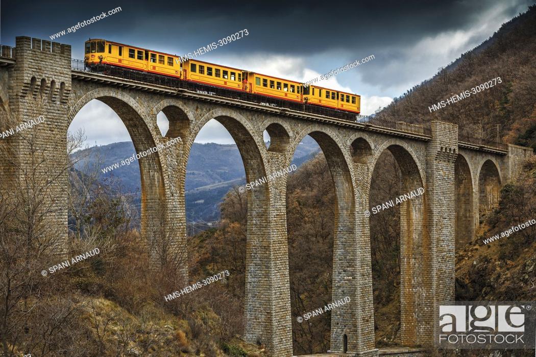 Stock Photo: France, Pyrenees Orientales, Natural regional park Catalan Pyrenees, Tet Valley, Sejourne bridge, Le Train Jaune, rain crossing the bridge Sejourne in winter.