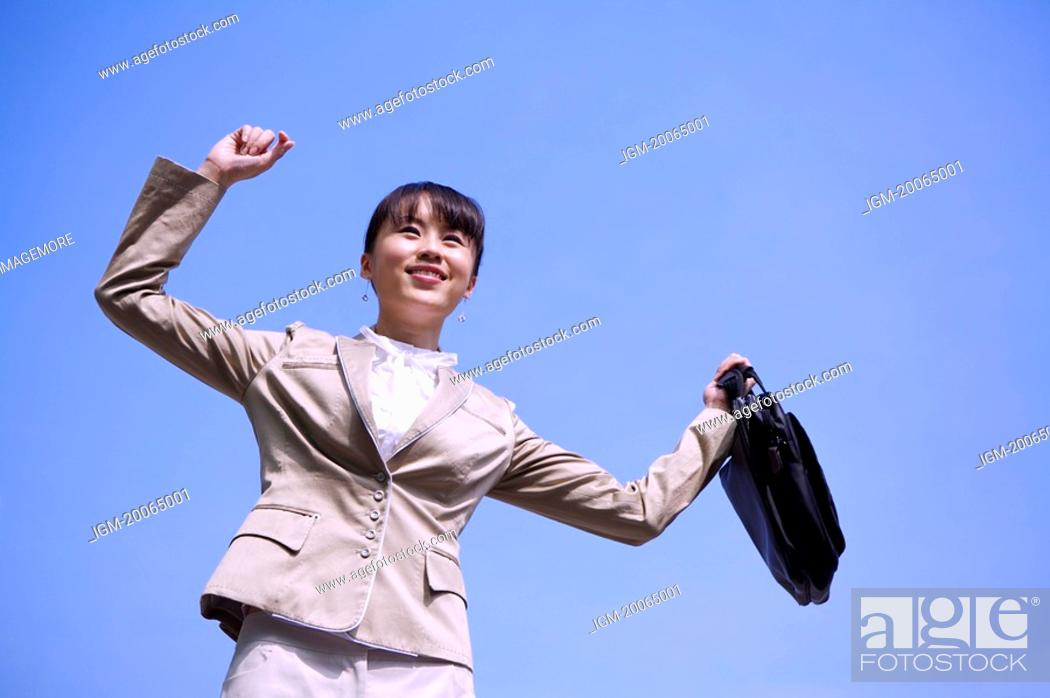 Stock Photo: Young businesswoman holding briefcase with arms outstretched and looking away with smile.