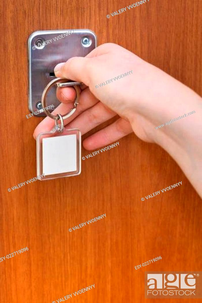 Photo de stock: opening home door by key with blank keychain.