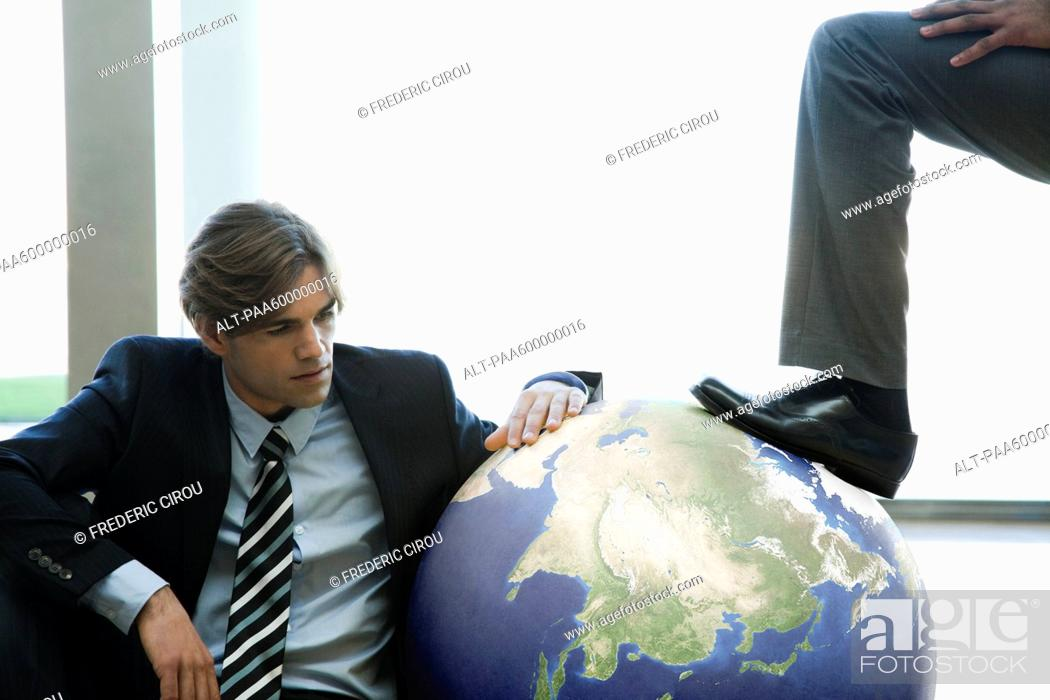 Stock Photo: Businessman stepping on ball while colleague watches.
