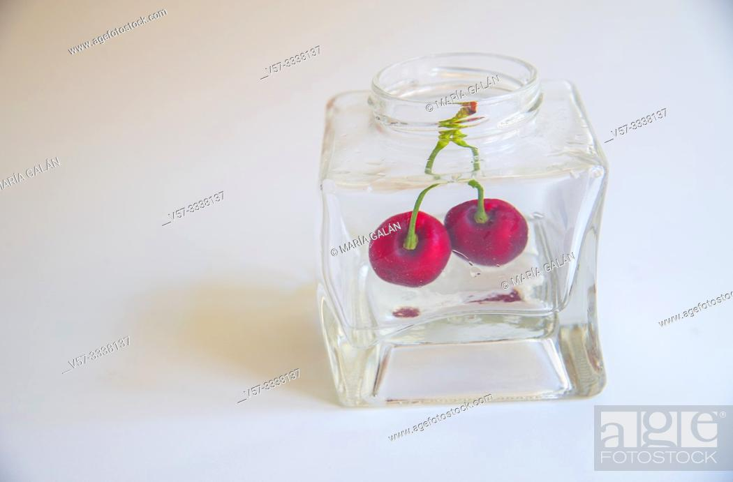 Imagen: Two cherries in a glass jar.