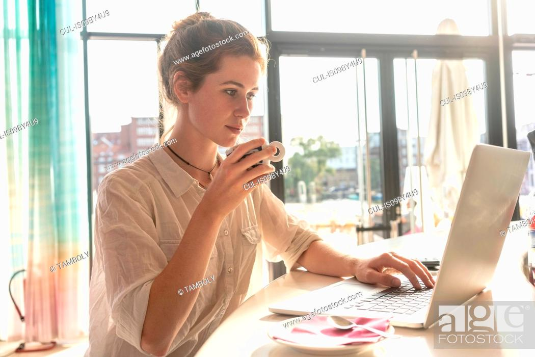 Stock Photo: Young woman using laptop and having coffee in office on sunny day.