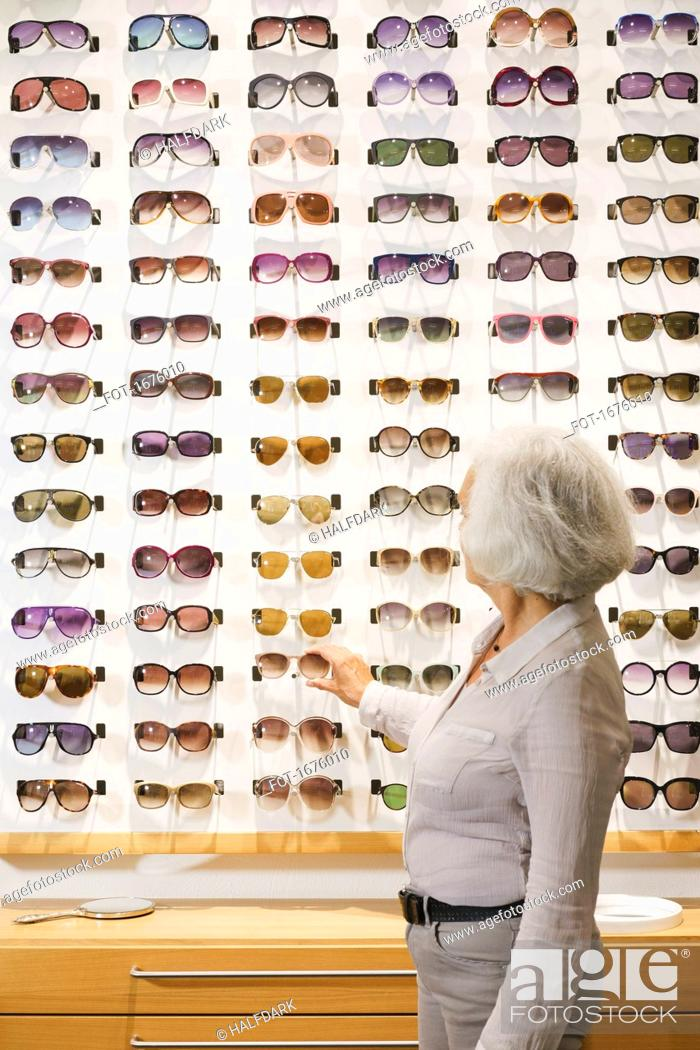 Stock Photo: Side view of senior woman choosing sunglasses at store.