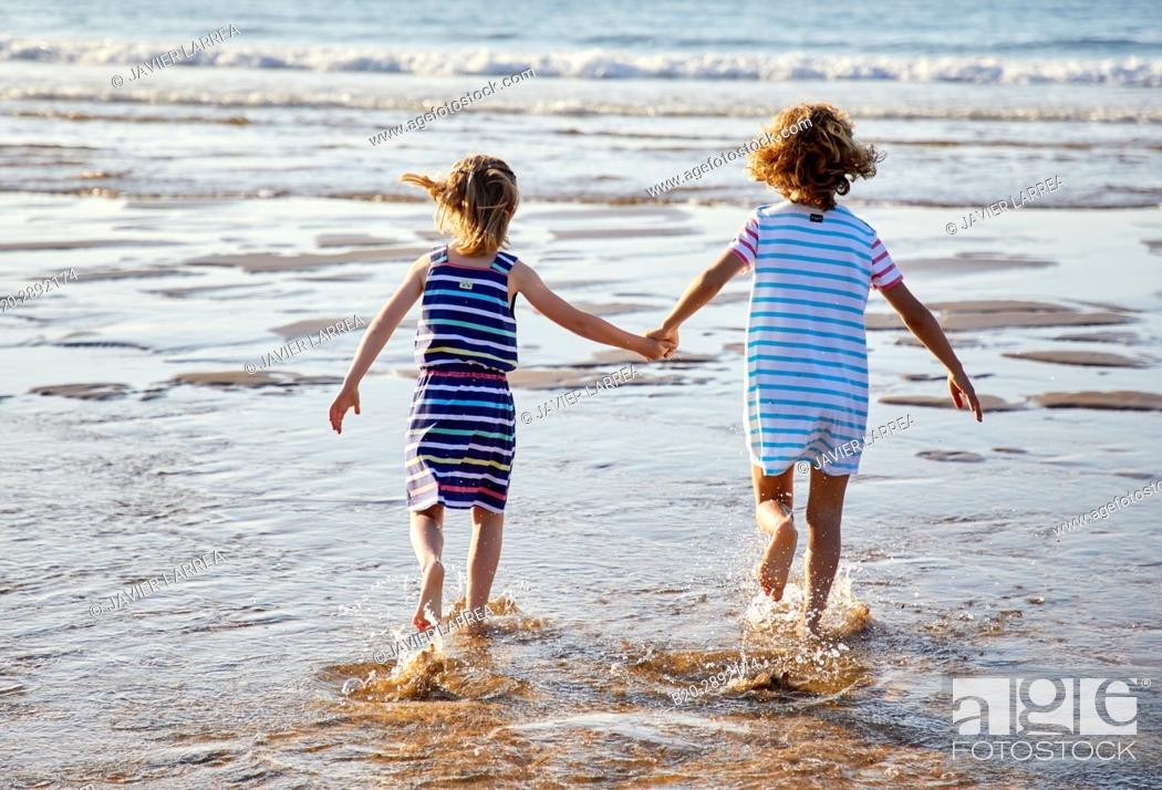 Stock Photo: Girls playing on the beach, Zarautz, Gipuzkoa, Basque Country, Spain, Europe.