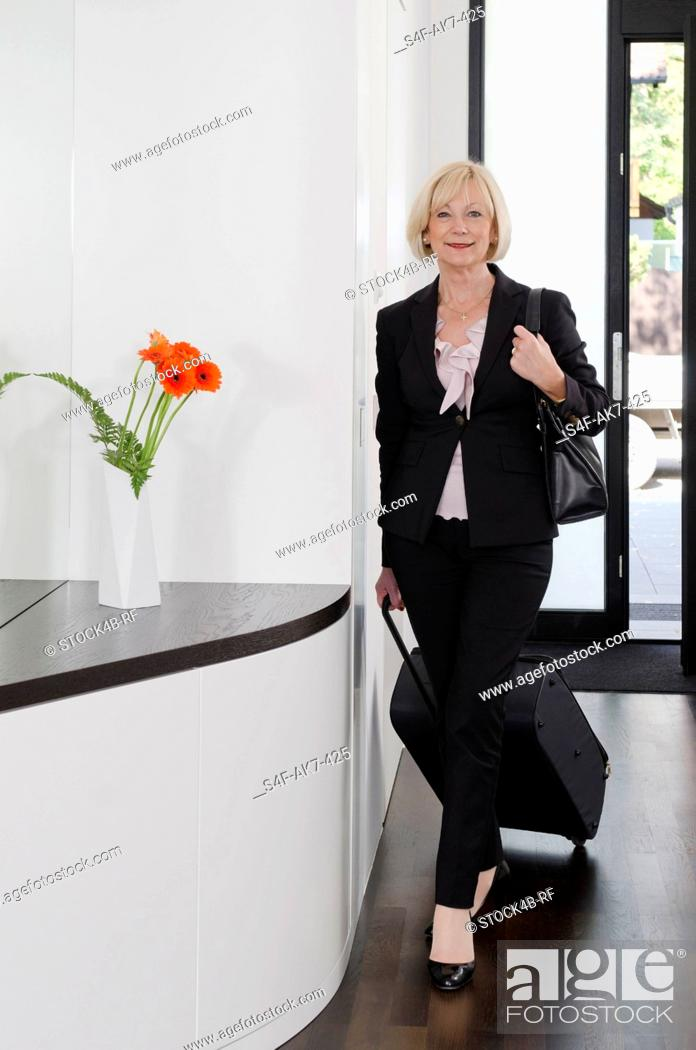 Stock Photo: Elegant woman with baggage standing in doorway.