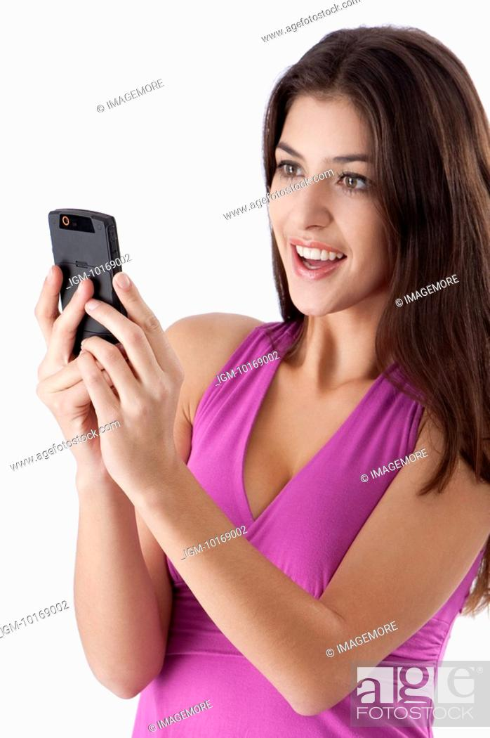 Stock Photo: Young woman looking at mobile phone happily.
