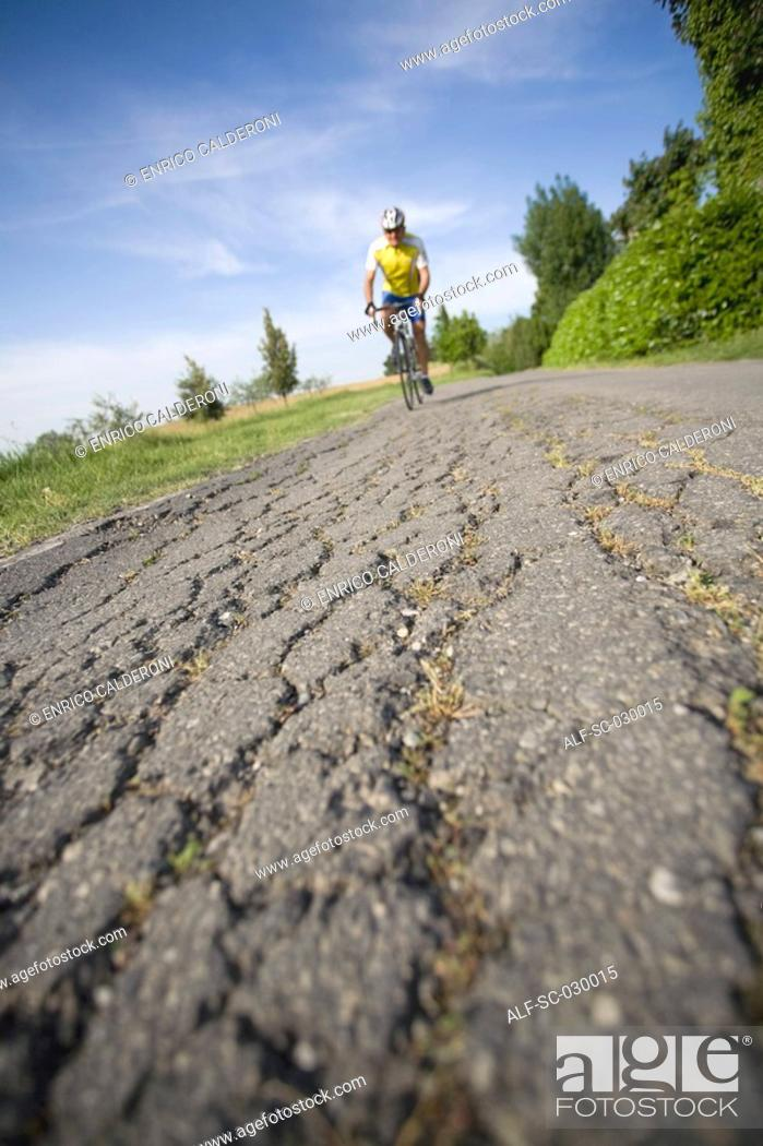 Stock Photo: Cyclist riding bicycle on a cracked road, front view.