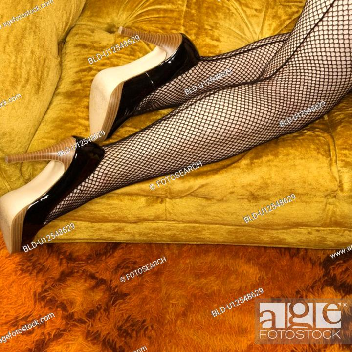 Stock Photo: Pretty woman in lingerie and fishnet stockings on sofa.