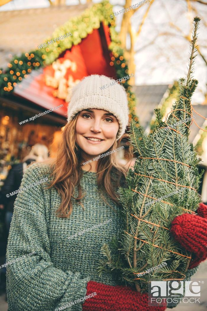 Stock Photo: Smiling woman with a wrapped-up tree standing on the Christmas Market.
