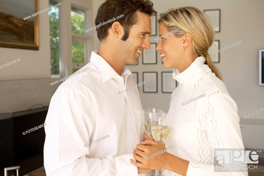 Stock Photo: Mid adult couple holding hands and drinking champagne.