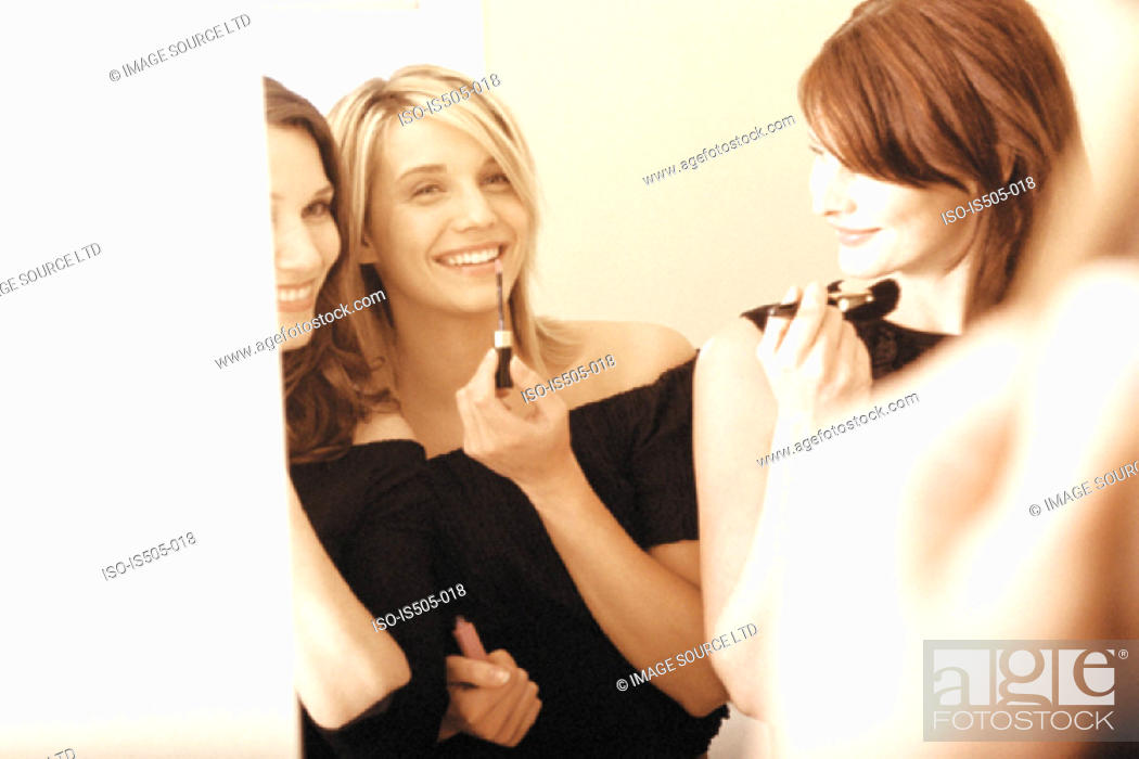Stock Photo: Women applying makeup.
