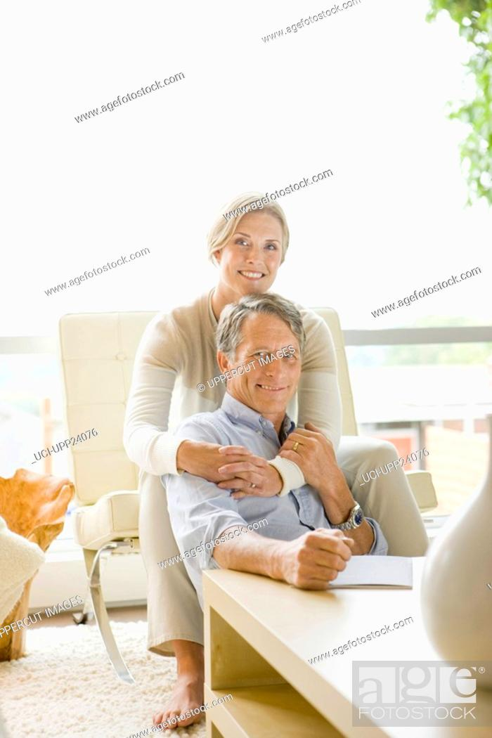Stock Photo: Portrait of couple hugging in living room.