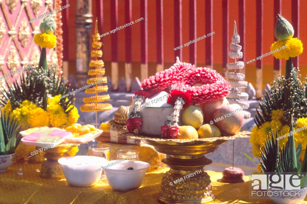 Imagen: offerings of fruit, rice, flowers at Buddhist temple, Thailand, to gain merit for the next life.