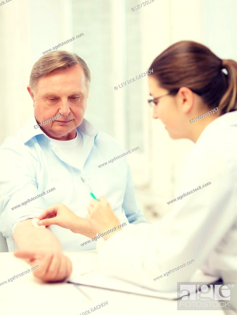 Stock Photo: healthcare, medicine and elderly concept - female doctor or nurse doint injection to old man.