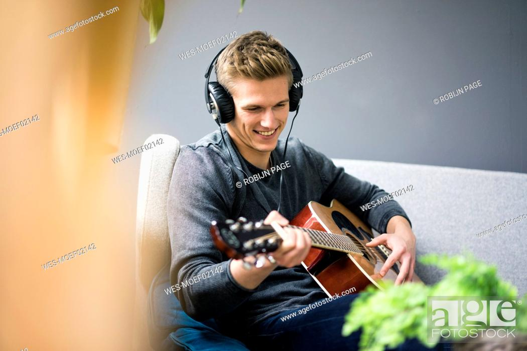 Imagen: Smiling young man with headphones sitting on couch playing guitar.