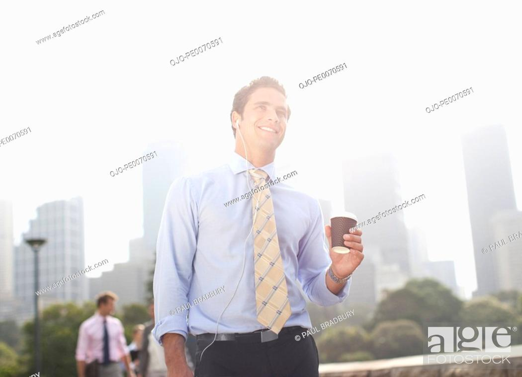 Stock Photo: Businessman carrying coffee outdoors.