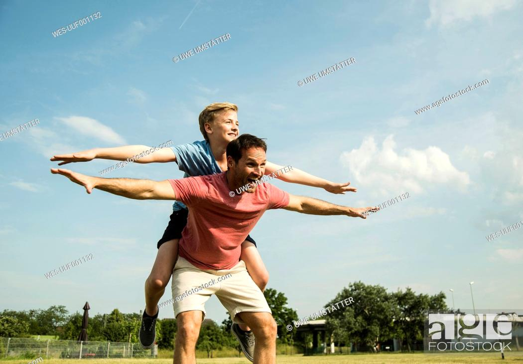 Stock Photo: Germany, Mannheim, Father and son pretending to fly.