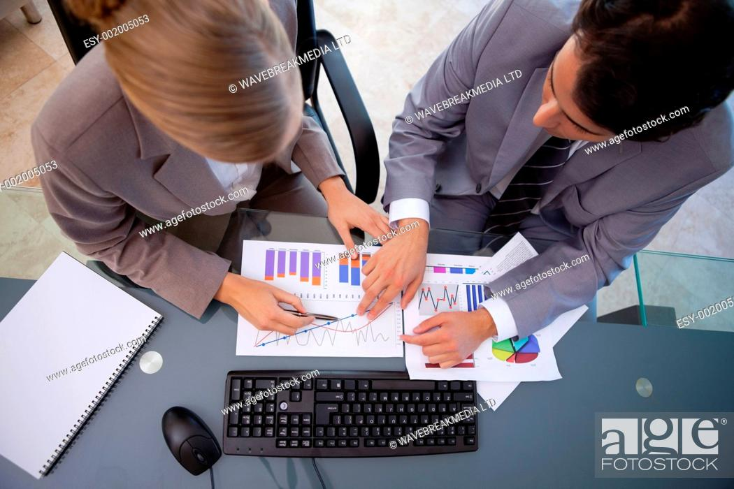 Stock Photo: Serisous business team studying statistics in a meeting room.