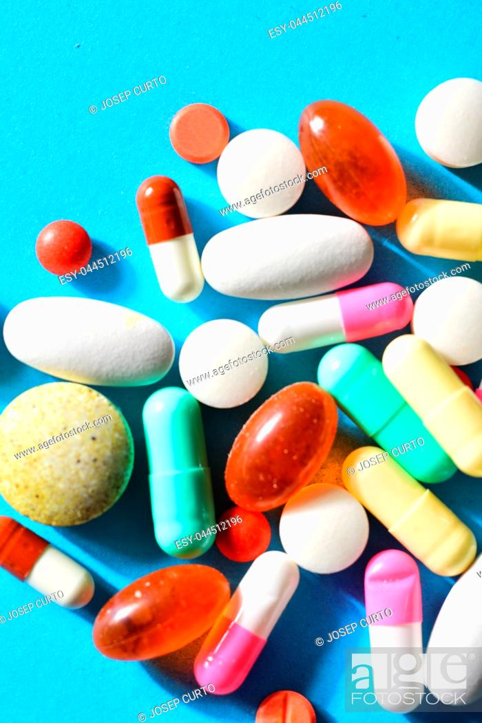 Stock Photo: group of varied pills on blue background.