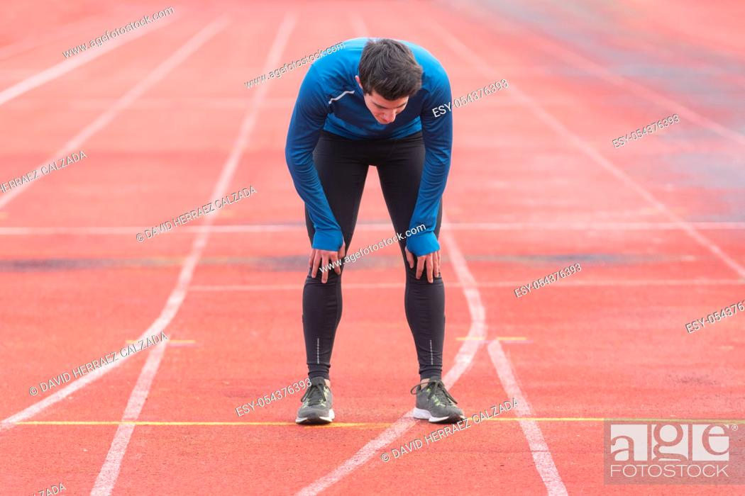Stock Photo: Athlete young man tired, resting on running track .