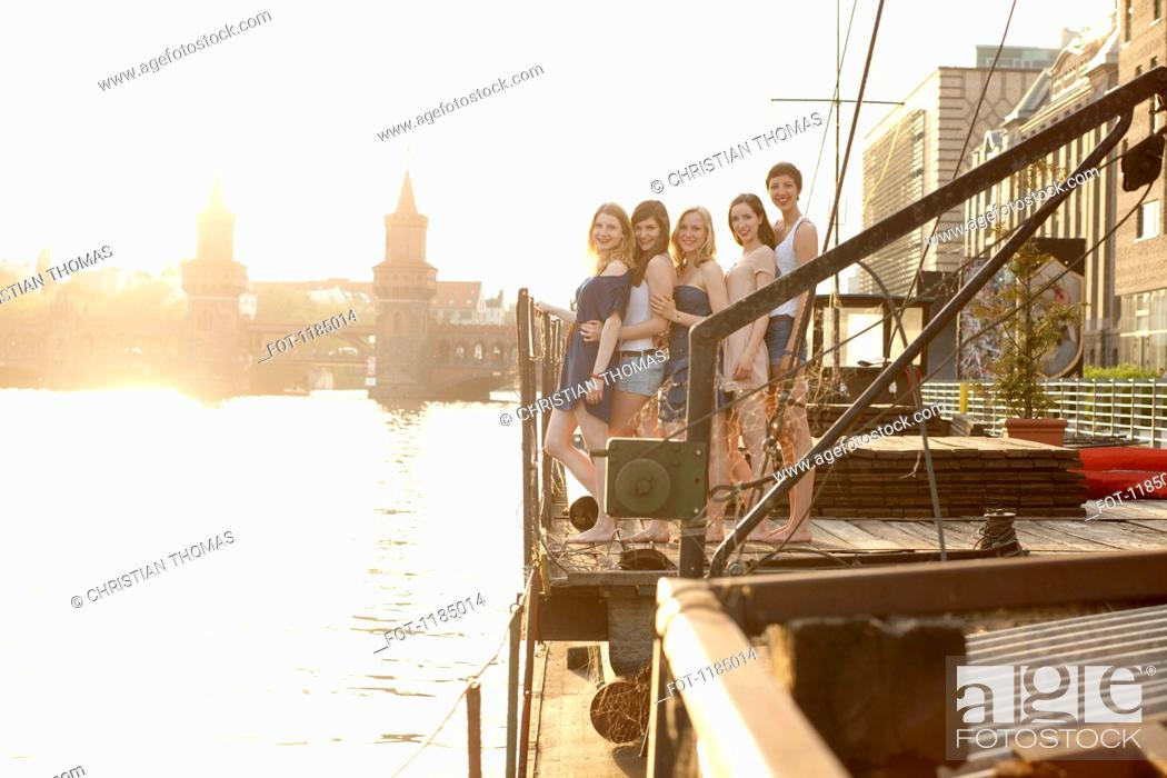 Stock Photo: Five female friends standing in a row on a jetty, Spree River, Berlin, Germany.