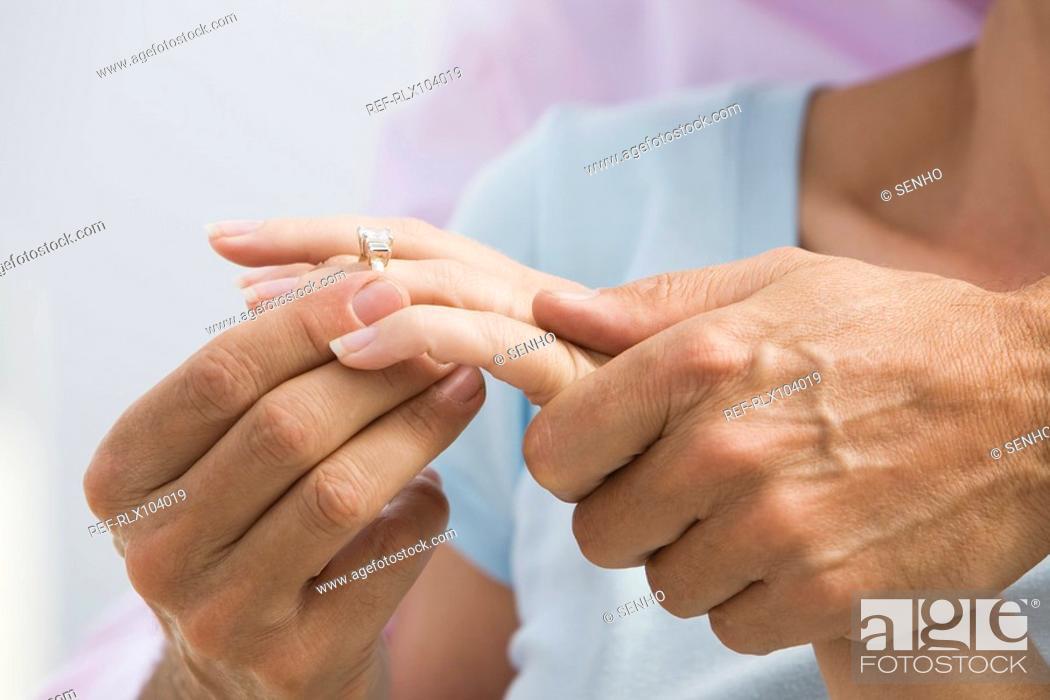 Stock Photo: Senior couple man putting diamond ring on woman's finger, detail of hands.
