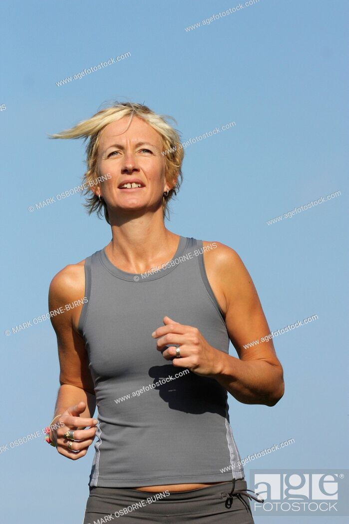 Stock Photo: Blonde woman outdoors. Close-up. Jogging in countryside.