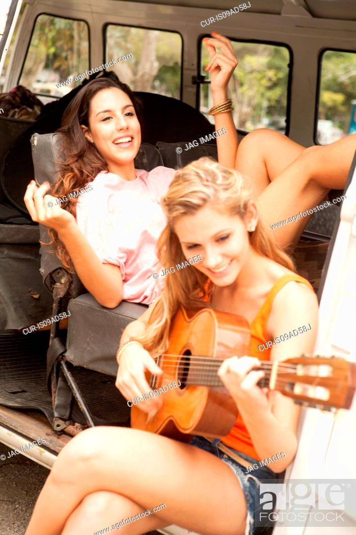 Stock Photo: Young women with guitar on camper van, Rio De Janiero.