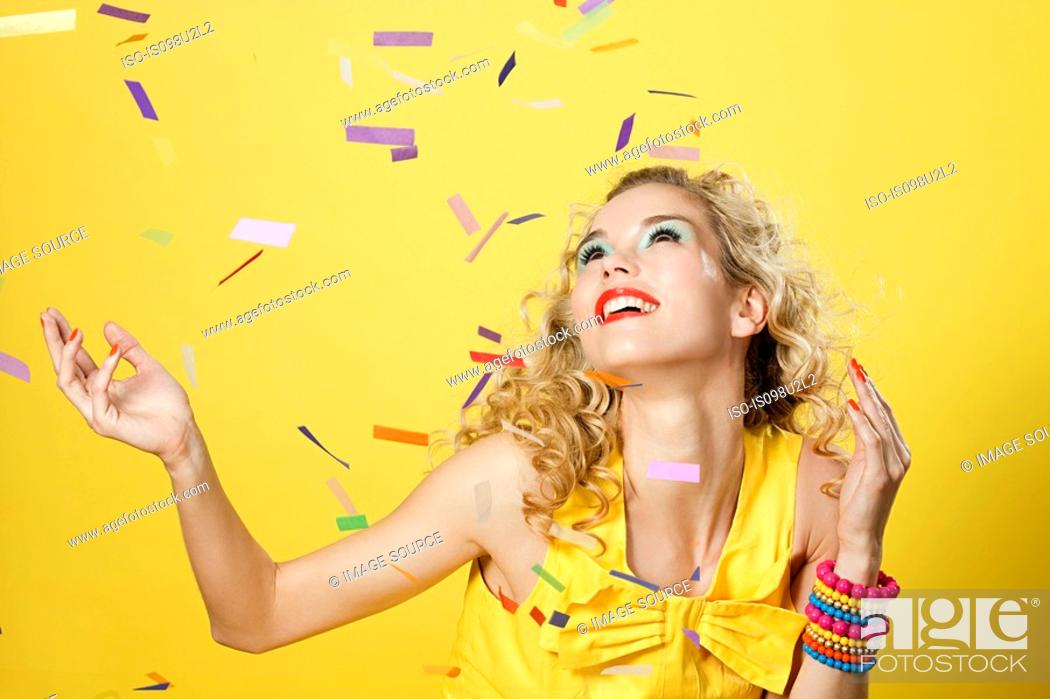 Stock Photo: Young blonde woman with colourful confetti.